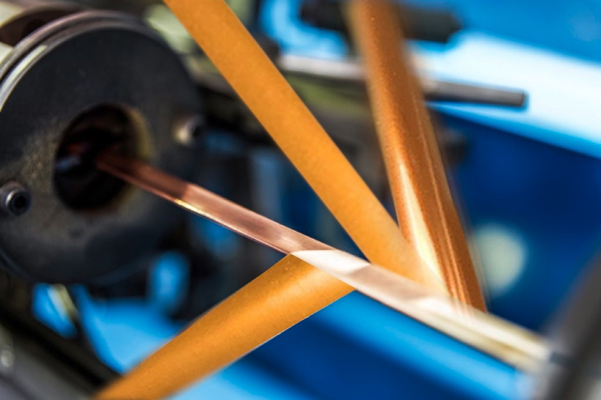 A machine is winding three layers of polyimide films onto a copper wire